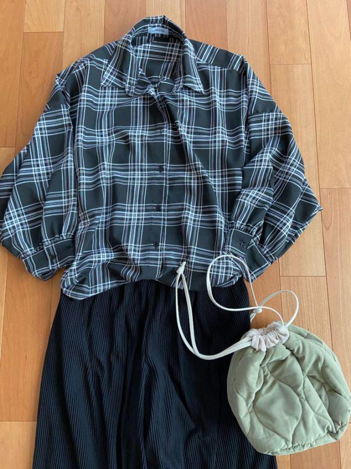 チェックのビッグシャツとパンツの上下黒のコーデに流行りの巾着バッグ